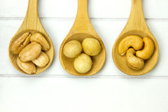Three wooden spoons filled with nuts Royalty Free Stock Photography