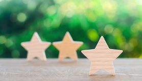 Three wooden stars on a green bokeh background. The concept of the rating of hotels and restaurants, the evaluation of critics and. Visitors. Quality level royalty free stock images