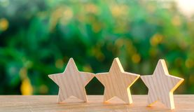 Three wooden stars on a background of green bokeh background. The concept of the rating of hotels and restaurants, the evaluation. Of critics and visitors royalty free stock photos