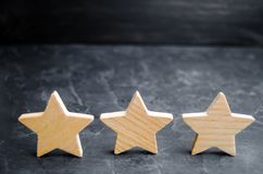 Three wooden stars on a black background. The concept of the rating of hotels and restaurants, the evaluation of critics and visit. Ors. Quality level, good royalty free stock photo