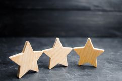 Three wooden stars on a black background. The concept of the rating of hotels and restaurants, the evaluation of critics and visit. Ors. Quality level, good royalty free stock images