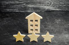 Three wooden stars and a house. Three star hotel or restaurant. Review of the critic. Quality of service and level of service. Rating of houses and private royalty free stock image
