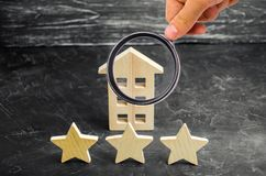 Three wooden stars and a house. Three star hotel or restaurant. Review of the critic. Quality of service and level of service. royalty free stock image