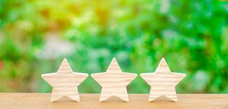 Three wooden stars. The rating of the hotel, restaurant, mobile application.The concept of rating and evaluation. Quality service,. Buyer choice. Success in stock photos