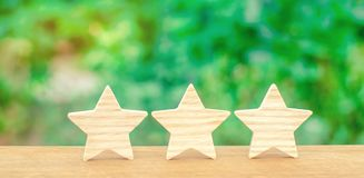 Three wooden stars. The rating of the hotel, restaurant, mobile. Application.The concept of rating and evaluation. Quality service, buyer choice. Success in stock photo