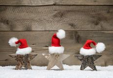 Three wooden stars with santa hats on wooden background Royalty Free Stock Photography