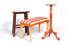 Three wooden stools stand on white floor Royalty Free Stock Images