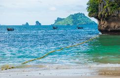 Three wooden Thai boats a long tail in the sea mooring stock photo