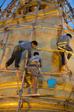 Three workers cleaning the gigantic golden stupa. Inside Saket temple in Bangkok in June 23, 2017 Royalty Free Stock Photography