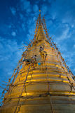 Three workers cleaning the gigantic golden stupa. Inside Saket temple in Bangkok in June 23, 2017 Royalty Free Stock Images
