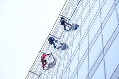Three workers cleaning windows service on high rise building stock images