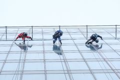 Three workers cleaning windows service on high rise building royalty free stock images