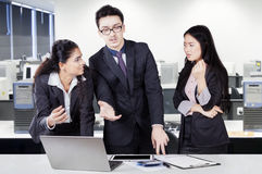 Three workers debating in the office Stock Photo