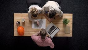 Three workers discuss plan of building and watch laptop, teamwork concept, office concept, communication concept stock footage