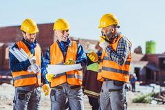 Three workers in hardhats examining building plans and talking on portable radio. At construction site royalty free stock photo