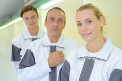Three workers in matching overalls. Matching Royalty Free Stock Photo