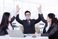 Three workers raising arms up Stock Images