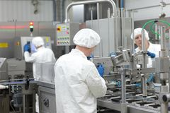 Three workers in uniforms at production line in plant. Teamwork royalty free stock photography