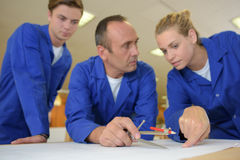 Three workers using compass Royalty Free Stock Photos