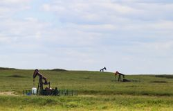 Three working pump jacks on oil or gas wells out in a green field royalty free stock photography