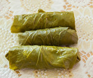 Three wrapped pieces of meat in green vine leaves a decorated board Stock Images