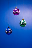 Three xmas balls on blue Stock Photography