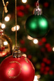 Three Xmas Baubles. Shot in front of a Christmas Tree Stock Photos