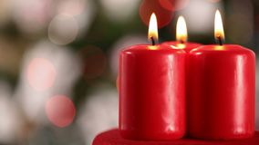 Three xmas candles burning in front of blurry xmas lights stock footage