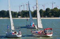 Three yachts moving in the same direction along the rive Stock Photos
