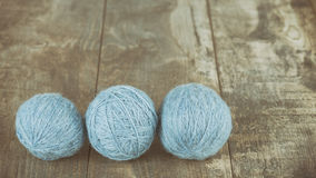 Three yarn balls on a wooden background. Royalty Free Stock Photos