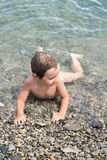 Three year boy bathes in the sea on pebbles Stock Photo