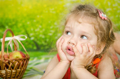 The three-year girl looked up at the picnic Royalty Free Stock Image
