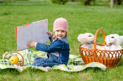 The three-year girl showing a book on a picnic Stock Image