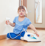 Three year old baby playing with  iron Stock Photo