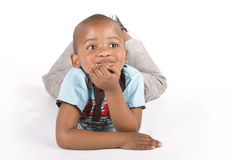 Three year old black boy lying down smiling Stock Photos