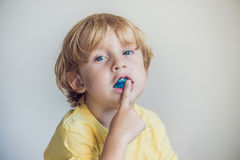 Three-year old boy shows myofunctional trainer to illuminate mouth breathing habit. Helps equalize the growing teeth and correct. Bite. Corrects the position of stock photography