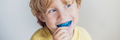 Three-year old boy shows myofunctional trainer to illuminate mouth breathing habit. Helps equalize the growing teeth and correct b. Ite. Corrects the position of royalty free stock photography