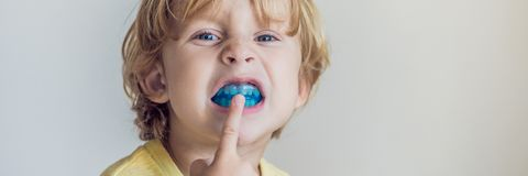 Three-year old boy shows myofunctional trainer to illuminate mouth breathing habit. Helps equalize the growing teeth and. Correct bite. Corrects the position of stock images