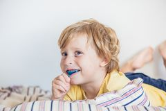 Three-year old boy shows myofunctional trainer to illuminate mouth breathing habit. Helps equalize the growing teeth and correct b. Ite. Corrects the position of Royalty Free Stock Images
