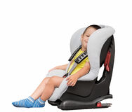 Three-year-old boy sits in an automobile children`s chair Royalty Free Stock Photography