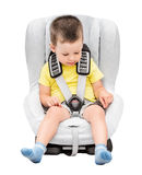 Three-year-old boy sits in an automobile children`s chair Royalty Free Stock Image