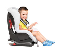 Three-year-old boy sits in an automobile children`s chair Stock Photos