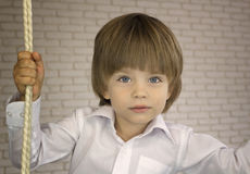 Three-year-old boy in a white shirt with rope Stock Photos