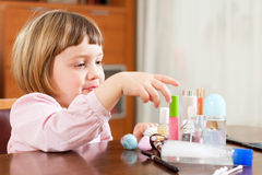 Three year old child painted cosmetics. Little cute girl playing with makeup Stock Photo