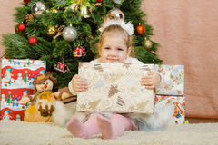 Three year old girl with a big gift from the Christmas tree Stock Photos