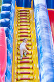 Three year old girl climbs on a big inflatable trampoline Stock Photo