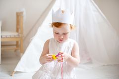 Three-year-old girl in the crown plays Royalty Free Stock Photography