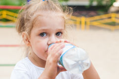 Three year old girl drinks from a bottle. At the playground Royalty Free Stock Image