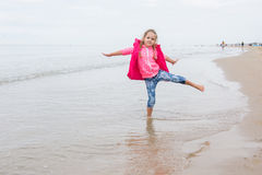 Three year old girl having fun stood on one leg on the beach. In the cool overcast weather Stock Image