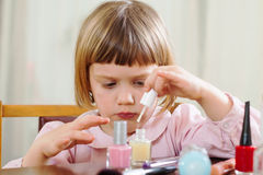 Three year old girl making manicure Stock Photo